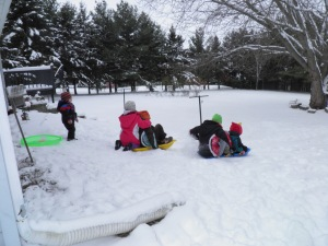 All of the kids going sledding at Grandma's