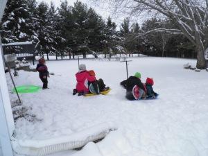 All of the kids going sledding at Grandma's