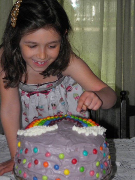 Iris trying to steal a Skittle off of her cake!